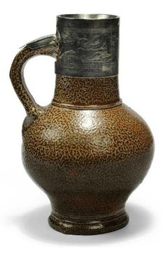 A RHEINISH SALT-GLAZED 'TIGERWARE' JUG WITH SILVER MOUNTS  LATE 16TH/17TH CENTURY.  Of globular form with short cylindrical neck and loop handle, covered in a lustrous mottled brown glaze, the silver collar engraved with various birds including a dove, eagle and peacock amongst flowering branches, with the initials 'LF' over 'SF', the top part of the handle fitted with a thumb-rest engraved with a stylised leaf