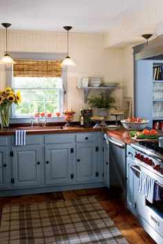 Cozy and Cheerful A mix of old and new warms this Sag Harbor cottage's country kitchen, with mahogany countertops, stainless-steel appliances, and the dusty blue cabinets. Creamy beadboard walls and open shelves keep the room light.