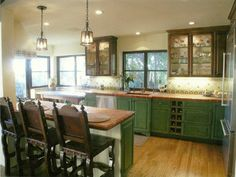 View of kitchen showing counter seating, sink,  built in wine storage, stained cabinets.