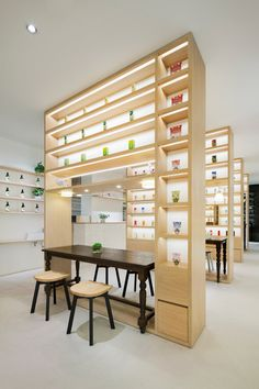 Beauty Library by Nendo. Beauty products are displayed on rows of shelves arranged like a library inside this Tokyo cosmetics store by Japanese design studio Nendo. This cosmetics store also incorporates a cafe, where food and drinks are prepared behind a long service counter that runs down one side of the shop.