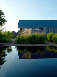The blackened reflecting pool sits at the heart of the garden. On one side is this weathered oak garage, designed by Bradley-Hole and flanked by the tall grass Calamagrostis x acutiflora 'Karl Foerster', which keeps its shape in winter.-- Front Garden at Bury Court, photo Clive Nichols. Gardenista