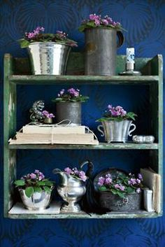 Silver and pewter containers filled with violets (looooove violets) but this also shows how well pewter items do compliment the old blue furniture!!