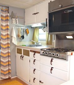 With cool grays, soft yellows, and clean lines, this vintage camper has a mid-century mod vibe thanks to a remodel by Meseidy Rivera at The Noshery. The bright and cheery space features newly painted cabinets, fresh upholstery on the benches, and a new laminate wood floor. See more at The Noshery.    - CountryLiving.com