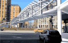 The West Thames Street Pedestrian Bridge, scheduled to open above West Street in late 2016, will be surrounded by mesh fencing and feature a double lenticular truss. Rendering: Economic Development Corp.