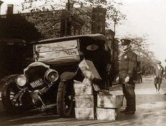 Policeman standing alongside wrecked car and cases of moonshine