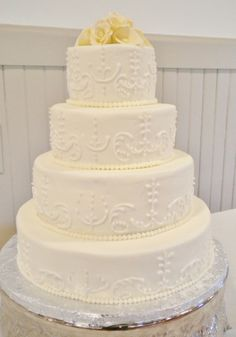 Buttercream iced tiers with modeling chocolate flower topper