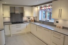modern kitchen installed in Ipswich by debenvale. with cream gloss doors and soft grey worktops and floors