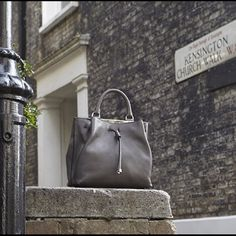 Mulberry Small Grey Kensington The Small Kensington is an elegant and modern interpretation of a drawstring satchel. A striking metal bar and otherwise minimal decoration keeps the silhouette fresh and uncluttered, but still eternally chic. The style consists of two symmetrical compartments to easily organise contents, each secured with a magnetic closure. The detachable shoulder strap allows for a choice of versatile carry options. Tres chic! Mulberry Bags Satchels