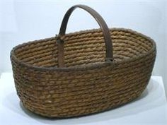 """ca 1890 This oval rye straw is a rare find among Pennsylvania baskets. The body is coiled rye straw held together with oak splint. Once the base was formed an oak handle was attached with the same oak splint binding. Rye Straw Baskets are rarely found with wooden bail handles, and are sought after by many basket collectors.     L. 12 1/2"""" X 7 1/2"""" W. X 4 5/8""""to top of straw & 7 3/4""""to top of handle"""