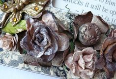 Here is a close-up view of some of the flowers and a meal button, all altered with paint and mica powder. (To alter the mulberry paper flowers, mist with water, then dust on Mica Powder. )