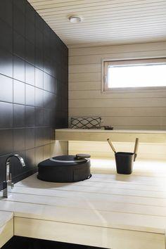 Saunan heti valmis kiuas on Helon Rondo ja seinällä on samaa mustaa laattaa kuin muissa pesutiloissa. Hana on Tapwellin mallistosta.