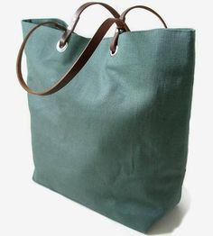 A sturdy everyday bag for notebooks and reading material, a laptop and paperwork or beach weekend getaway materials, this linen tote is roomy but lightweight enough to carry daily. The muted greenish grey linen pairs perfectly with the brown leather handles, the tote neutral enough to wear with any outfit.