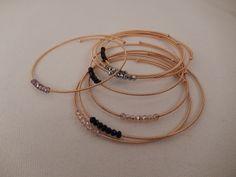Bracelets dorés rigides décorés de perles façon Christal noir, argenté, gris, mauve.
