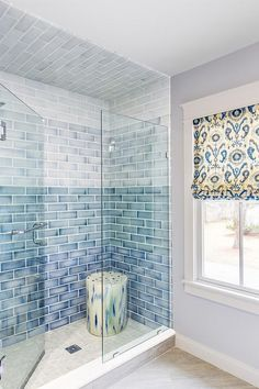 Your shower can be a spa-like space with the right tile. This shower features seamless glass door that opens to a walk-in shower clad in blue ombre ceramic tiles alongside a cream and blue stool placed atop a cream tiled shower floor. Design by ACQUIRE Glass Tile Shower, Blue Glass Tile, Bathroom Floor Tiles, Bathroom Showers, Bathroom Marble, Bathroom Ideas, Tile Showers, Bathroom Baskets, Glass Tiles
