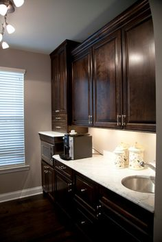 Dark stained cabinets, dark floors, marble tops, grey walls. Basement bar area? I think yes!