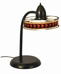 Home Theater Accessories and Unique Cinema Decor Movie Reel Desk Lamp with Theater Film 35 MM Description:Uses a x steel teardrop reel with real film edge Includes a mini bulb. Theater Room Decor, Home Theater Rooms, Home Theater Seating, Movie Reels, Film Reels, Movie Film, Hollywood Room, Desk Lamp, Table Lamp
