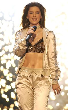 """Abs for Days from Shania Twain's Sexiest Looks  Only fitting that she wears fancy workout wear to show off those impressive abs, here  performing """"I'm Gonna Getcha Good"""" during VH1's Big In '03 concert."""