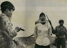 A South Vietnamese soldier with a knife interrogates a young woman about the location of Viet Cong units in the area, 1967.