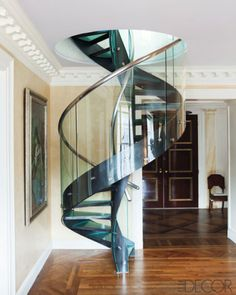 Contemporaryfoyer with staircase fabricated in molded glass, resin, and stainless steel leads from the main floor of a Manhattan apartment to the top floor. From Elle Decor