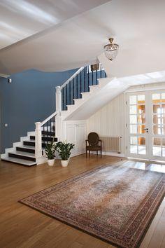 Hol wejściowy został połączony ze strefą dzienną. Dzięki temu jest ona jeszcze bardziej przestronna. Tuż obok znajdują się schody na poddasze. Fot. Monika Filipiuk-Obałek