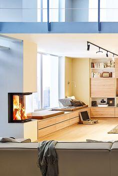 Ein moderner Kamin im Panorama-Format gibt dem Wohnraum nicht Gemütlichkeit und eine wohltuende Atmosphäre. Er gibt dem Raum auch einen innenarchitektonischen Mittelpunkt. Eine Feuerstelle, um die man sich gerne versammelt. Schön!