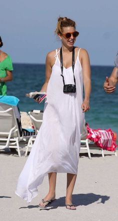 Whitney Port, in a white dress with a camera hung around her neck, takes a stroll on the beach in Miami, FL.  'The City' actress and celebrity fashion designer is in town for the Mercedes-Benz Swim Fashion Week.
