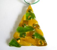 This listing is for a yellow and green fused glass Christmas tree ornament handmade for you in my Portland glass studio. It comes with a green raffia ribbon so its all ready to hang on your tree or in your window! It would make a fun gift tie or stocking stuffer, as well. This ornament measures about 2.5 wide at the bottom and about 2.75 tall (see third photo for size reference). Listing is for one ornament shown alone in the first three photos. I have these in other colors so stop by my…