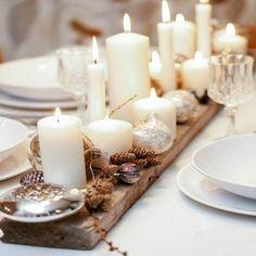 Un centre de table en bois avec des bougies chaleureuse pour une déco Noël conviviale.