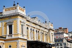 Photo made at the historic and elegant building of the station of Trieste in Friuli Venezia Giulia (Italy). In the image you can be seen the upper part of the side and the front of the train station. And in addition to the blue of the sky on the horizon other palaces.