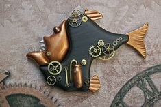 STEAMPUNK HATCHETFISH  There are two types of hatchetfish. One is a tropical freshwater species and the other lives in the deepest and darkest depths of the ocean. My hatchetfish is the second version, where some of the strangest and most fantastic creatures live.  This deep sea hatchet fish is made of exotic cocobolo wood, polymer clay, and lots of old watch gears and brass rods. Polymer Clay Projects, Polymer Clay Creations, Punk Costume, Steampunk Animals, Cardboard Toys, Polymer Clay Animals, Punk Goth, Steampunk Clothing, Steam Punk Jewelry