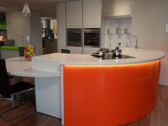 White gloss handle-less kitchen with orange Perspex detail, LED strip lighting and curved Corian worktops (located in KAM Design showroom)