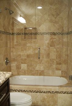 stone enclosed tub - frameless glass shower doors - glass mosaic trim :)