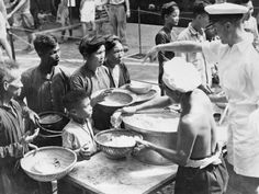 The aircraft carrier HMS WARRIOR evacuates 1,455 refugees from Haiphong, North Vietnam to Saigon during Operation PASSAGE TO FREEDOM, 4 September 1954. Rice and other food is issued to refugees in the forward lift well .