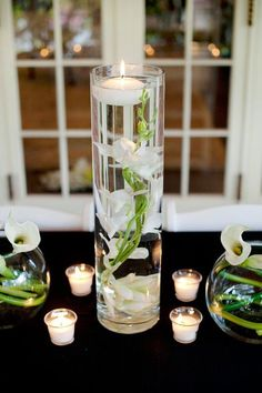 DIY Centerpiece Ideas. Fill a tall cylinder vase with water and add a white orchid. Top with a floating candle.