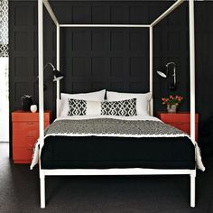 Black bedroom with accents. Dark charcoal panelling, a white bed, plus black and white patterned fabric create a monochromatic theme that's punctuated with orange cabinets.  #Sleeptember