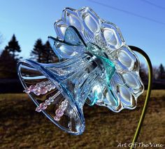 BEAUTIFUL FLOWERS MADE OF PLATES, BOWLS, VOTIVES OR WHATEVER GLASS OBJECTS THAT MAKE A GORGEOUS FLOWER...
