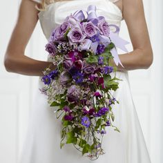 This blissful purple wedding bouquet has lavender roses at the top and pink orchids and carnations to compliment. It's finished off with suspended ivy vines to create a magical effect.