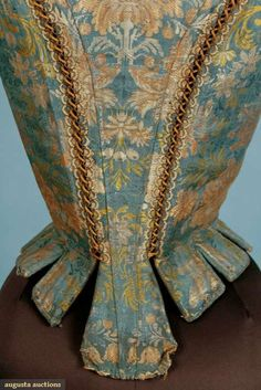 "LADIES' SILK BROCADE STAYS, 1700-1720 French blue silk w/ peach, ivory,  green brocade, CF eyelets to have laced to stomacher, short cap sleeve, cane boning, stays constructed in 3 pieces joined at CB w/ double row of metal eyelets laced w/ cord, tabbed hem, home-spun linen lining, B 21.5"",W 20"", CBL 17.25"", (shoulder area possibly altered)"