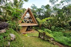 An eco bamboo house in Bali, Indonesia, nestled in the mountains of a volcano featuring a water wheel to provides water and electricity, tropical eco bamboo decor, hammocks, and Balinese textiles.