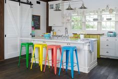 """Zippy bursts of solid colors, like the row of candy-hued stools at the kitchen island and the apple green cupboard that peeks up from the rest of the white cabinetry, are lively without overwhelming the room. """"Using larger chunks of color versus small, intricate patterns makes a bolder statement that's also easier on the eye,"""" says interior designer Michelle Fries, who helped Jenny plan the space. RELATED: 101 Kitchens We Love"""