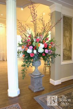 Urn arrangement on pedestal with white hydrangea, orange and pink gerbera daisies, pink roses, bells of Ireland, pink snapdragons, pink peonies, and blooming branches.