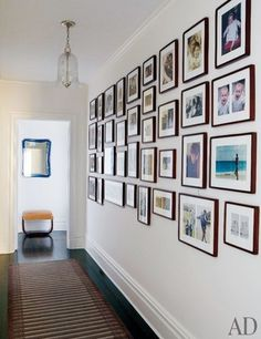 A gallery-style wall of family pictures is the focal point of this minimalist hallway in the Manhattan home of Michael J. Fox and Tracy Pollan. Using warm wood frames and clean white mats—an effective way to visually unify a wall of photos—showcases their collection of full-color and black-and-white images with elegance.