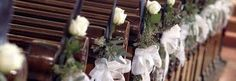 Simple rose and ribbons decorated chairs to line the aisle.