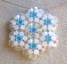 Snowflake Pendant  Required materials and tools of the pendant:  - 30 x 6 mm polished beads   - 42 pcs 4mm Swarovski crystal beads   - seed beads   - wire   - csomórejtő   - stopwatch   - fishing line   - beading needle   - scissors