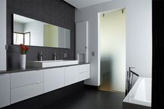 Modern bathroom design & lighting. The tiled backsplash along the entire wall has a fantastic texture.