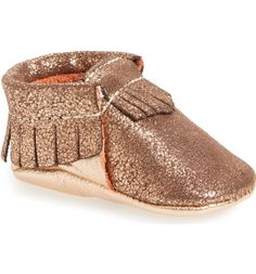 Fringe trim and a shimmery rose gold finish make this moccasin-style crib shoe an instant favorite.