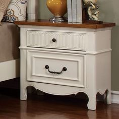 This sweet and simple nightstand is designed to create a light-hearted yet functional bedside storage area. The cottage style wood paneling enhances the chic white finish while the cherry finished surface accentuates the wood craftsmanship.