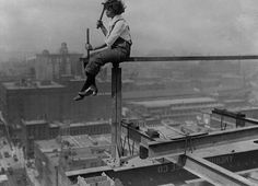 Female worker (probably a model for a photo op) atop the Wrigley Building, under construction, 1920, Chicago