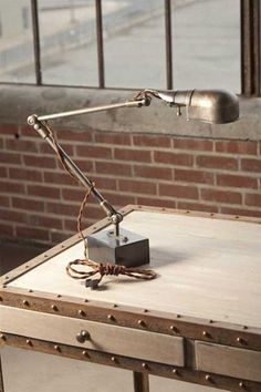 This vintage-inspired task lamp is the perfect industrial touch for a desk or work-area in the office, wood shop or living room. The adjustable arm and shade are made of distressed metal and sit upon