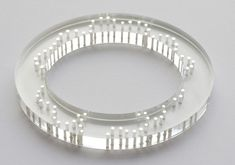 Silver rivets catch the light and create patterns on the surface of the perspex bangle. Perspex and Silver.